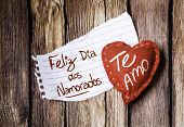 "stock photo of miss you  - ""Feliz Dia dos Namorados, Te Amo"" (In portuguese - Happy Valentines Day, I Love You) written on a peace of paper and a heart on a wooden background - JPG"