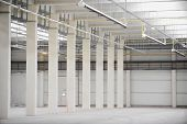 picture of floor heating  - Interior detail with an empty industrial storage depot with ceiling heating system  - JPG