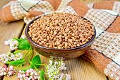 stock photo of buckwheat  - Buckwheat in a bowl with a flower buckwheat and a napkin on a wooden boards background - JPG
