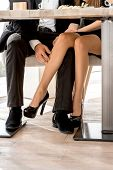pic of flirt  - Young couple flirting with legs at the restaurant under the table - JPG