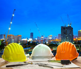 picture of land development  - engineer working table with hard hat plan and writing tool against beautiful lighting and urban building construction site use for land and city development backgound - JPG