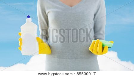 people, housework, washing-up and housekeeping concept - close up of woman holding sponge and cleanser bottle over blue sky and cloud background