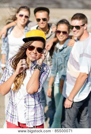 summer holidays and teenage concept - teenage girl in sunglasses, cap and headphones hanging out with friends outside