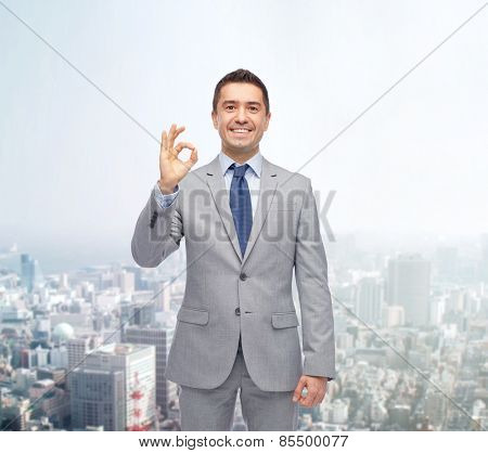 business, people, gesture and success concept - happy smiling businessman in suit ok hand sign over city background
