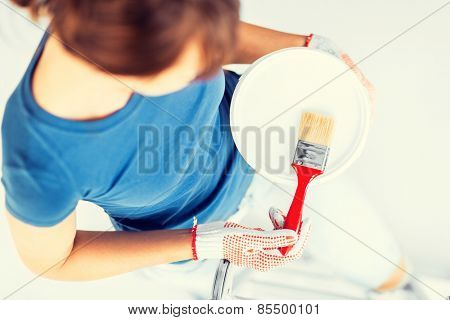 interior design and home renovation concept - woman with paintbrush and paint pot