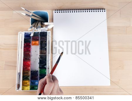 Beautiful composition of watercolor paints, brushes, album artist, with the artist's hand.
