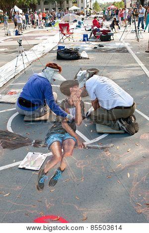 Chalk Artists Draw Halloween Scene On Street