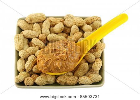 A spoon of creamy crunchy peanut butter on peanuts isolated on white