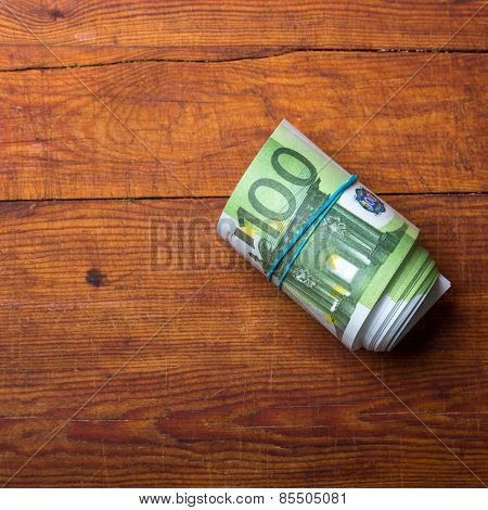 Roll of one hundred euro banknotes on wood background