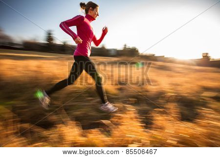Young woman running outdoors on a lovely sunny winter/fall day (motion blurred image)
