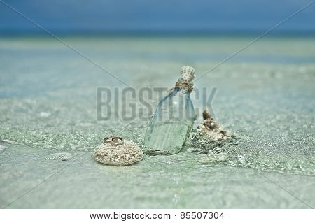 Two wedding rings on the coral stone with the glass bottle and sea shells on tropic beach in Thailan