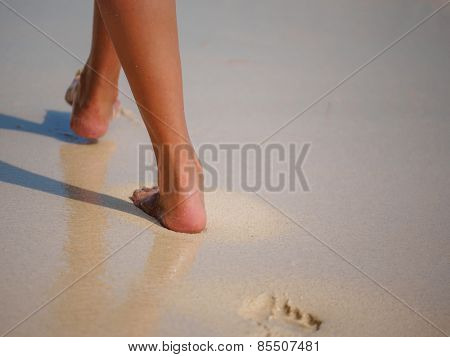 woman walking on sand beach leaving footprints in the sand. Closeup detail of female feet and golden sand