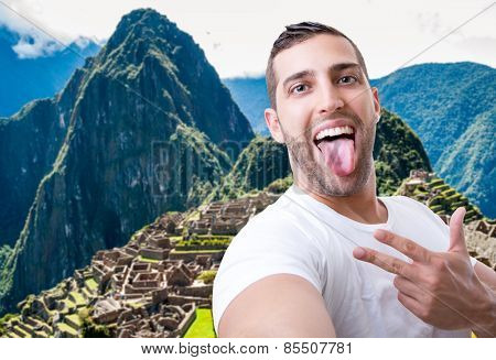 Happy young man taking a selfie photo in Machu Picchu, Peru