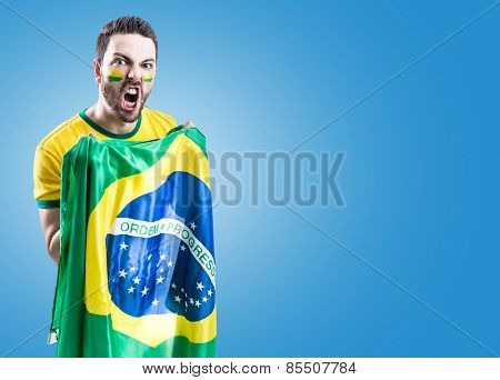 Man holding the Brazilian flag on blue background