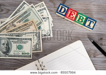 Top view bank notes , diary and debt alphabet blocks on old wooden desk.