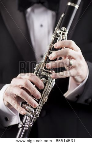 hands of man in tuxedo holding clarinet, room for copy