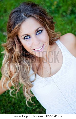 Cool pretty woman with white dress and a beautiful smile sitting on the grass