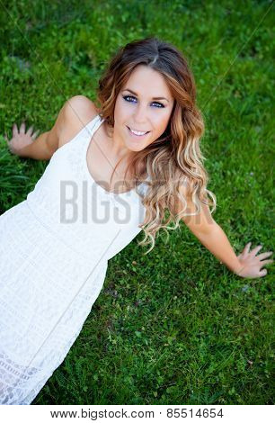 Cool pretty woman lying on the grass with a beautiful smile