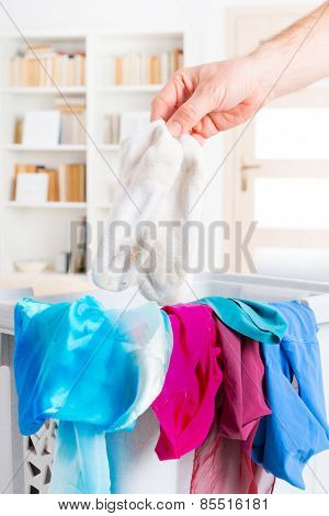 Hand holding dirty white socks over a hamper or basket