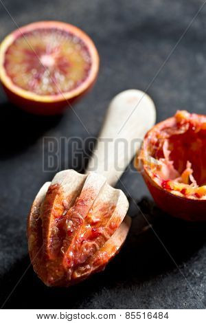 halved blood orange and juicer on black background
