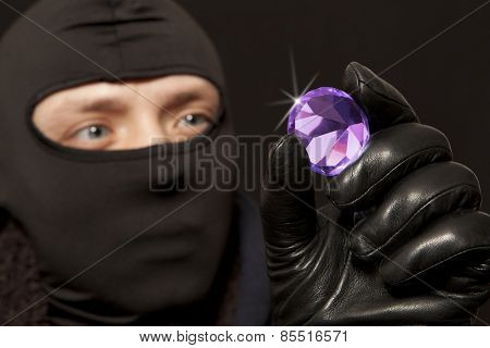 Thief. Man in black mask with a big diamond.Focus on diamond