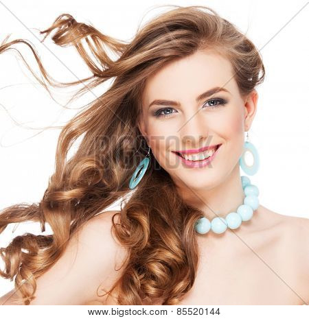 Beautiful woman with long curly brown hair. Glamour smiling female. Studio shot. streaming hair