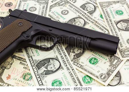 Gun On Money Background.