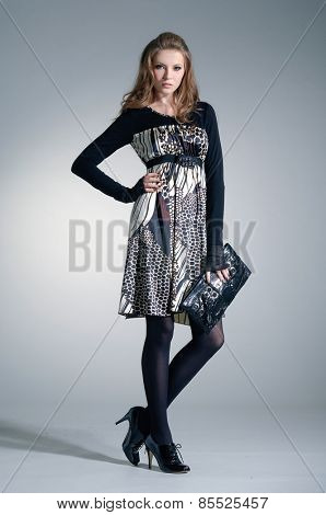 full-length fashion model in autumn/winter clothes holding handbag posing