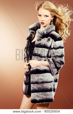 Fashion shot of a beautiful blonde woman wearing jewelry and fur coat. Studio shot.