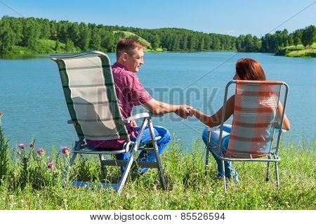 Portrait Of A Man And Woman Holding Hands, Sitting In Chairs Near The Lake