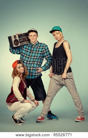 Group of young modern dancers dancing together with fun. Studio shot.