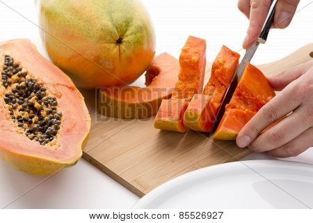 Half A Papaya Fruit Being Cut Into Slices