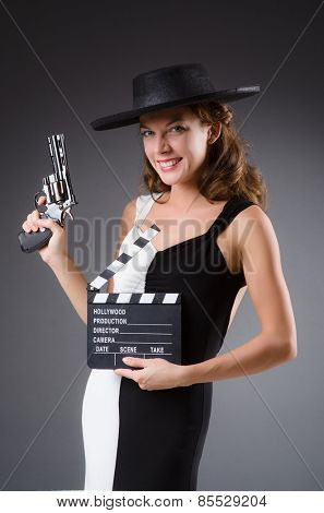 Girl with gun and clapperboard isolated on white