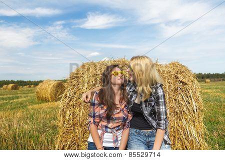 Girls enjoy sunny day on large round bale