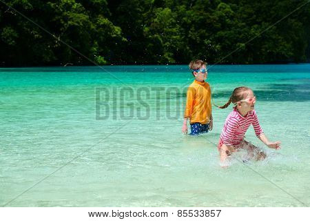 Two kids playing at at shallow water during summer vacation