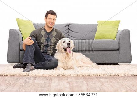 Young man sitting on the floor with his dog isolated on white background