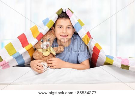 Playful kid holding a teddy bear under a blanket at home