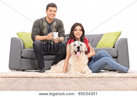 Young couple sitting with a dog on a modern sofa isolated on white background
