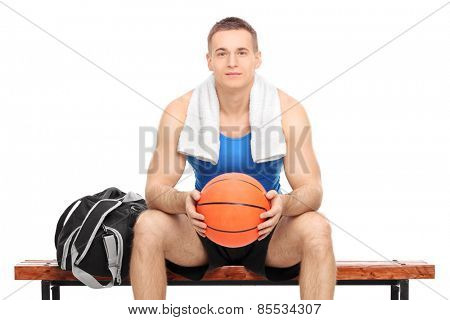 Young male basketball player sitting on a bench isolated on white background
