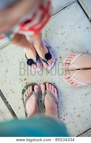 Top view of family mother and kids feet in flip flops on summer vacation
