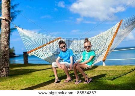 Brother and sister relaxing in hammock