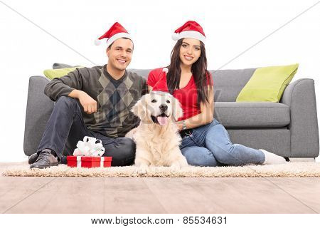 Couple with Santa hats sitting with a dog by a sofa isolated on white background