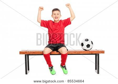 Joyful junior soccer player gesturing happiness seated on bench isolated on white background