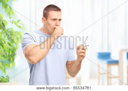 Young man smoking a cigarette and coughing at home