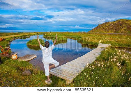Woman in white performs yoga. Iceland. Small pond with thermal water. In the smooth surface of the water reflects the sky and clouds