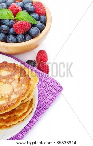 Pancakes with raspberry, blueberry, mint and honey syrup. Isolated on white background