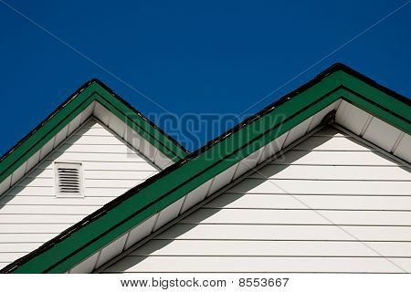 Two Farmhouse Roof Peaks With White Siding And Green Trim Against A Blue Sky.