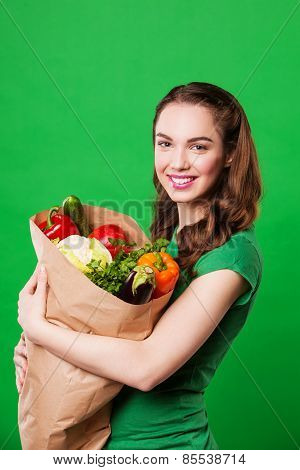 beautiful woman holding a grocery bag full of fresh and healthy food. on green background