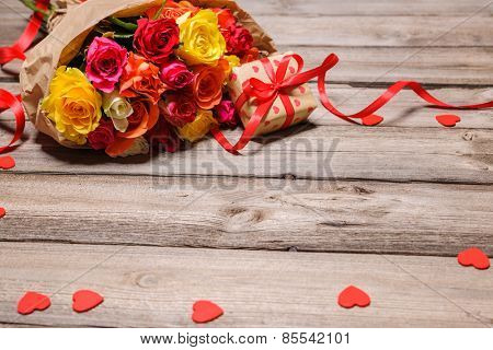 Bunch of roses with a gift box on weathered wooden background