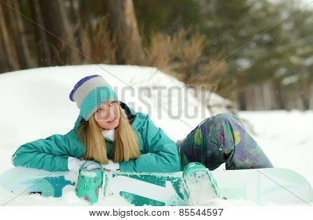 Girl with snowboard sitting on the snow